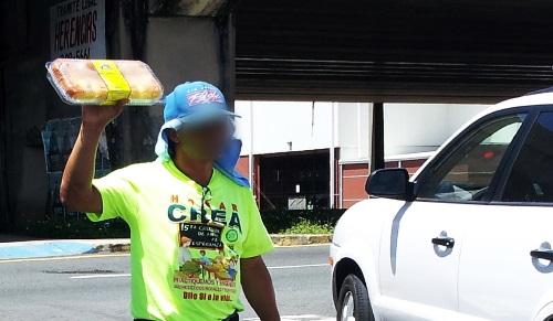"""Participante de Hogar CREA vende un bizcocho en un semáforo del área metropolitana. Foto por extraída del informe 'Humillación y abusos en centros de """"tratamiento"""" para uso de drogas en Puerto Rico'."""